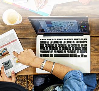 Laptop auf Tisch mit Händen und Tablet