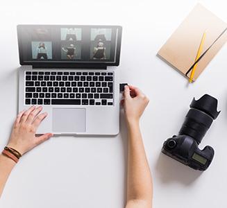 Tisch von oben mit Frau an Laptop und Kamerazubehör