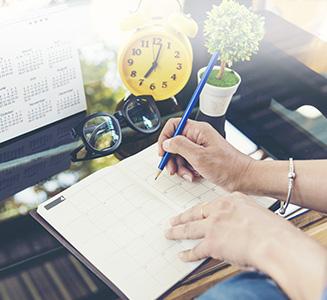 Frau mit Stift und Kalender an Tisch