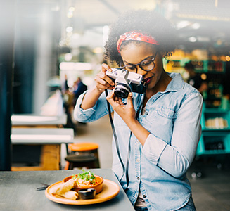 Frau in Restaurant fotografiert Essen