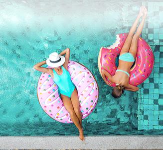 Mutter und Tochter auf Donuts im Pool