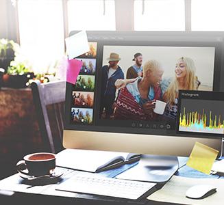 Schreibtisch mit Computer und geöffnetem Bearbeitungsprogramm