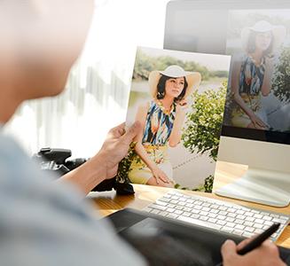Hand hält Bild vor Desktop PC