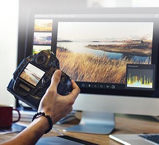 Kamera vor Desktop PC mit Bearbeitungsprogramm geöffnet