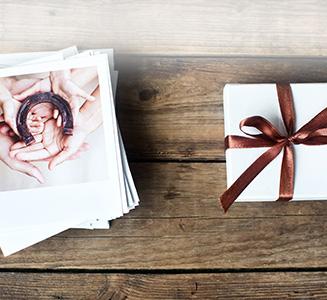 Polaroidstapel mit Geschenk auf Holztisch