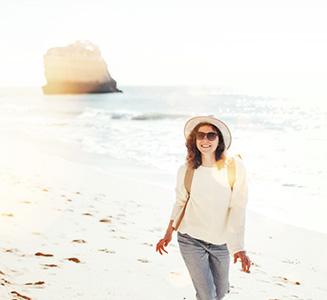 Frau mit Hut und Rucksack läuft am Strand mit Felsen