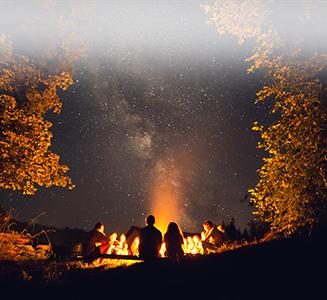Gruppe von Personen um Lagerfeuer bei Nacht mit Sternenhimmel