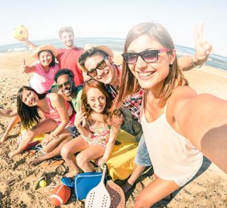 Freunde am Strand mit Sportartikeln