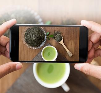 Hand hält Smartphone und fotografiert Tee
