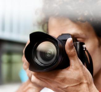 Mann hält Kamera mit Gegelichblende