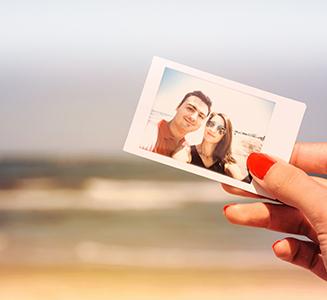 Frau mit rotem Nagellack hält Polaroid