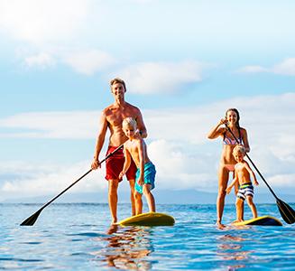 Familie mit Paddeln auf Boards im Wasser