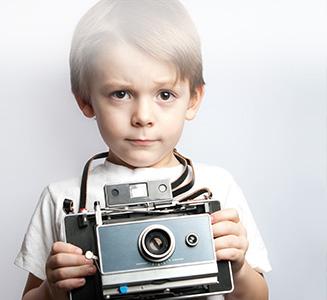 kleiner Junge mit analoger Kamera in Händen