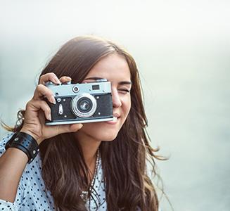 Junge Frau schaut durch Analoge Kamera