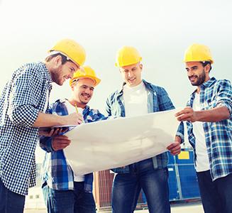 Männer mit Bauhelmen zeigen auf Bauplan