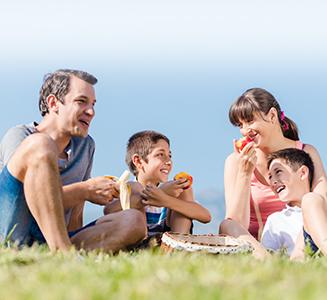 Glückliche Familie isst Piknik auf Wiese