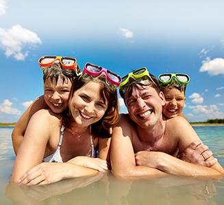 Glückliche Familie mit Taucherbrillen am Strand