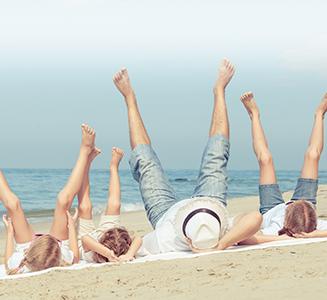 Familie hält am Strand Füße in die Luft