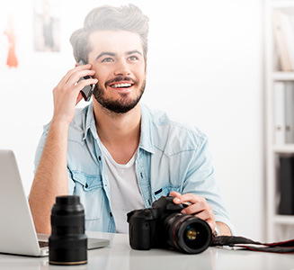 Mann telefoniert mit Kamera in Hand an Laptop