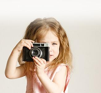 Kleines Mädchen mit analoger Kamera in Händen