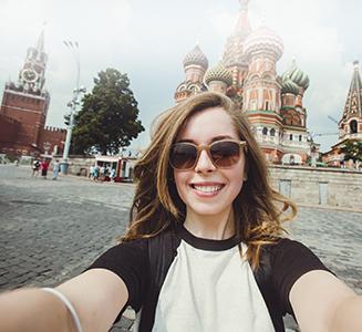 Frau mit Sonnenbrille in Moskau vor Basilius Kathedrale