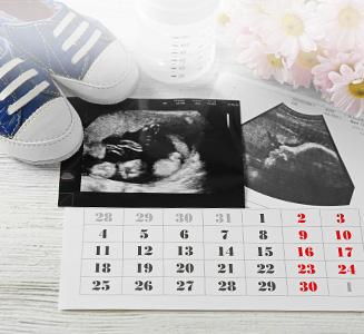 Kalender mit Ultraschallbild und Babyschuhen auf Holztisch
