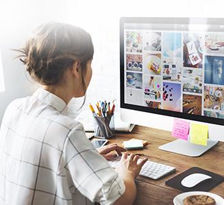 Frau sitzt vor PC am Tisch und schaut Bilder an