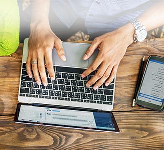Laptop auf Tisch mit Händen und Smartphone