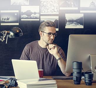 Mann mit Brille sitzt vor PC mit Objektiven