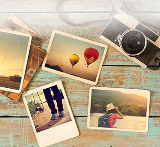 Alte Polaroids mit analoger Kamera auf Tisch