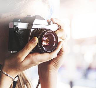 Frau hält Analoge Kamera mit Bokeh