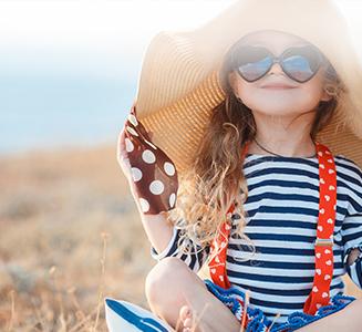 Kleines Mädchen mit Hut und Sonnenbrille auf Feld