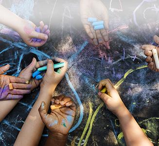 Kinderhände mit bunter Kreide über Tafel