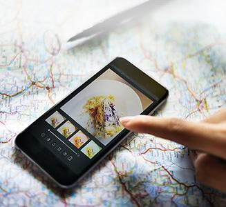 Person zeigt auf Smartphone mit Landkarte im Hintergrund