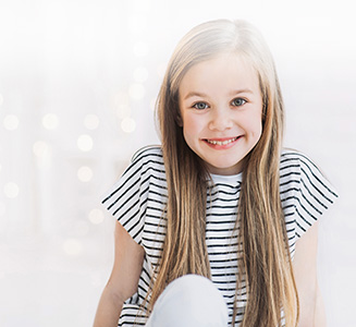 Kleines Mädchen mit langen Haare in gestreiftem Shirt