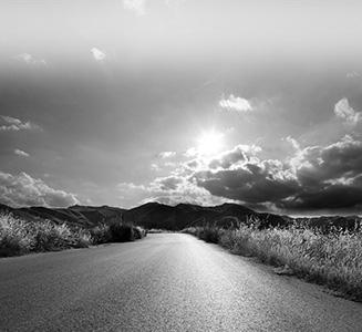 Straße mit Bergen und Sonne strahlt durch Wolken