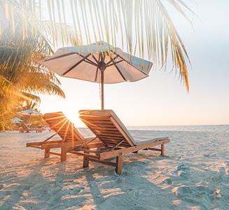 Liegestühle mit Sonnenschirm am Strand und Sonnenuntergang