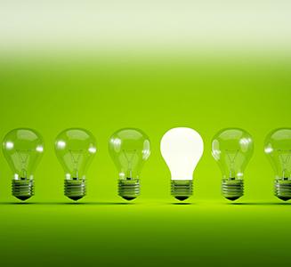 Glühlampen vor grünem Hintergrund eine brennt