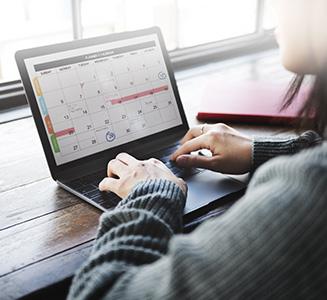 Frau tippt auf Laptop mit Kalender